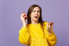Puzzled young woman in fur sweater looking up holding halfs of pitahaya, dragon fruit near ears isolated on violet stock photos