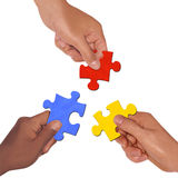 Puzzles. Difference races holding a puzzle Stock Photography