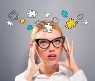 Puzzles with business woman. On a gray background Stock Photos
