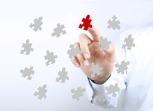Puzzles with businessman hand. Businessman hand is pointing the puzzles on the transparent virtual screen Royalty Free Stock Photos