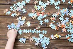 Puzzles, children`s hands with. preschool education. Puzzles, children`s hands with a puzzle on a wooden background. preschool education Royalty Free Stock Photos