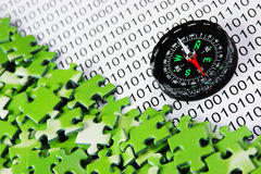 Puzzles and compass on a binary Stock Images