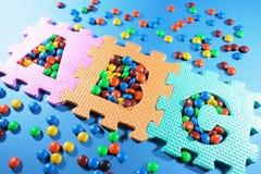 Puzzles d'alphabet et sucettes de chocolat Images stock