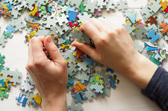Puzzles. Female hands folded puzzles Stock Photography