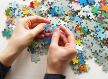 Puzzles. Female hands folded puzzles Royalty Free Stock Photos