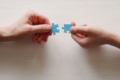 Puzzles. Hand of the child and hand of mother fold puzzle Stock Photo