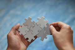 Puzzles and hands Stock Images
