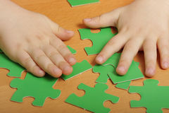Puzzles and hands. Hands and green puzzle pieces on a wooden tabletop Stock Photos