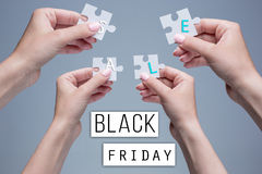 The puzzles in hands on gray. Background. Black Friday sale - holiday shopping concept Royalty Free Stock Image