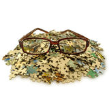 Puzzles on  pile, glasses to enhance visual acuity Stock Photo