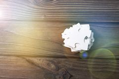 Pyramid of puzzles on a wooden background. Puzzles are placed on top of each other with a pyramid on a wooden background. A stack of details. puzzle. heap Stock Photos
