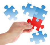 Puzzles. A red puzzle in hand and some blue puzzles on white background stock photo