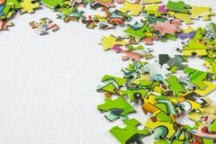 Puzzles scattered on a light table with the right close-up. Educational game for children and adults. Copy Space stock photo