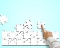 Puzzles se réunissants de main à l'arrière-plan bleu Photographie stock libre de droits