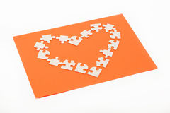 Puzzles in the shape of a heart on an orange. Royalty Free Stock Photo