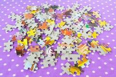 Puzzles sur un fond lilas Jeu de puzzles d'enfants Puzzles réglés Image stock