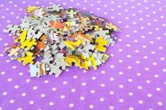 Puzzles sur un fond lilas Le bébé déconcerte le jeu Puzzles réglés Photographie stock