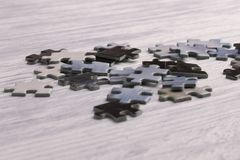 Puzzles on a white wooden table royalty free stock photography