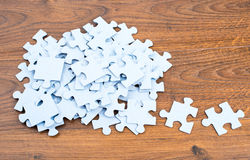 Puzzles on wooden background Royalty Free Stock Images