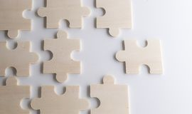 Last piece of wooden jigsaw is almost in place for business solu. Puzzles on a wooden background. Concept business. Idea: working in a team. Close up stock images