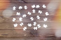 Puzzles on a wooden background. A group of puzzles are scattered chaotically on a wooden background. logical game Royalty Free Stock Image