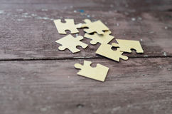 Puzzlespiel auf hölzernem Hintergrund lizenzfreie stockfotos