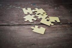 Puzzlespiel auf hölzernem Hintergrund Lizenzfreies Stockbild
