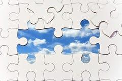 Puzzlespiel mit den fehlenden Stücken, die blauen Himmel aufdecken Stockfotografie