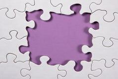 Puzzlespiel mit purpurrotem Hintergrund stockfotografie