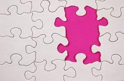 Puzzlespiel mit rosafarbenem Hintergrund lizenzfreie stockfotografie