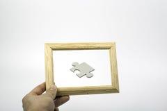 Puzzlespiel und ein hölzerner Beschaffenheitsrahmen Lizenzfreie Stockfotografie