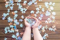 Puzzlespiele in den Händen eines Kindes Stockbild