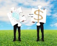 2 Puzzlespiele mit Idee zu halten ist Geldkonzept Stockfotos
