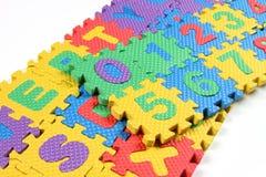 Puzzlespiele von Alphabeten und von Zahlen Stockbild