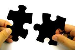 Puzzlespielstücke in den Händen Stockbilder