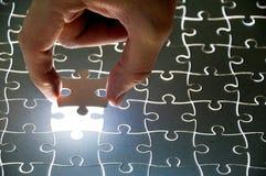 Puzzlespielstücke und -hand Stockbild