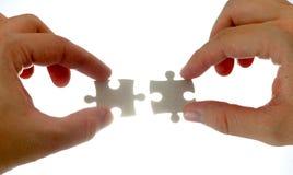 Puzzlespielstücke und -hand Stockfotos