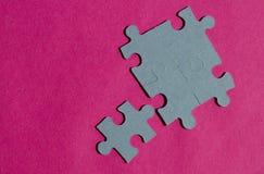 Puzzlestücke auf hellem rosa Hintergrund Stockbild