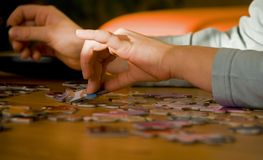 Puzzling. Close-up of the child's hands assembling puzzle Stock Image
