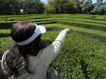 Puzzling maze. Woman points out route through maze Royalty Free Stock Photos
