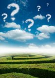 Puzzling World. A maze under a blue sky with question mark clouds Stock Photography