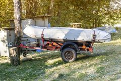 PVC inflatable boat under the tarp on the trailer royalty free stock photo