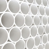 PVC pipes. Interesting perspective of new white PVC pipes stacked on a pallet stock photos