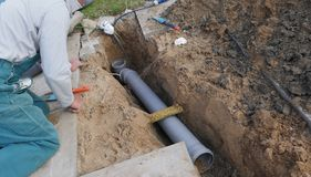 Laying and installation of a sewer pipe. PVC sewer pipe on a construction site stock photos