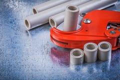 PVC-Wasserleitungsschneider auf metallischem constructi Draufsicht des Hintergrundes Stockfotografie