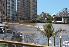 PWCs-Zoom über dem Brisbane-Fluss nahe der berühmten Geschichten-Brücke und Eagle Street Pier mit Wolkenkratzern im Hintergrund i Lizenzfreies Stockfoto
