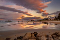 Pink twilight over wet sand beach stock images