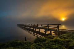 Jetty with reflection in foggy dawn stock photos