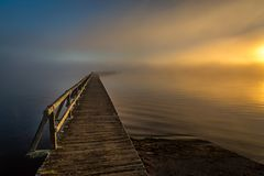Old wood jetty reaching into foggy lake in morning twilight royalty free stock images