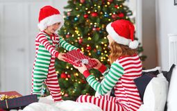 Py family mother hug her baby son in pajamas opening gifts on c stock image